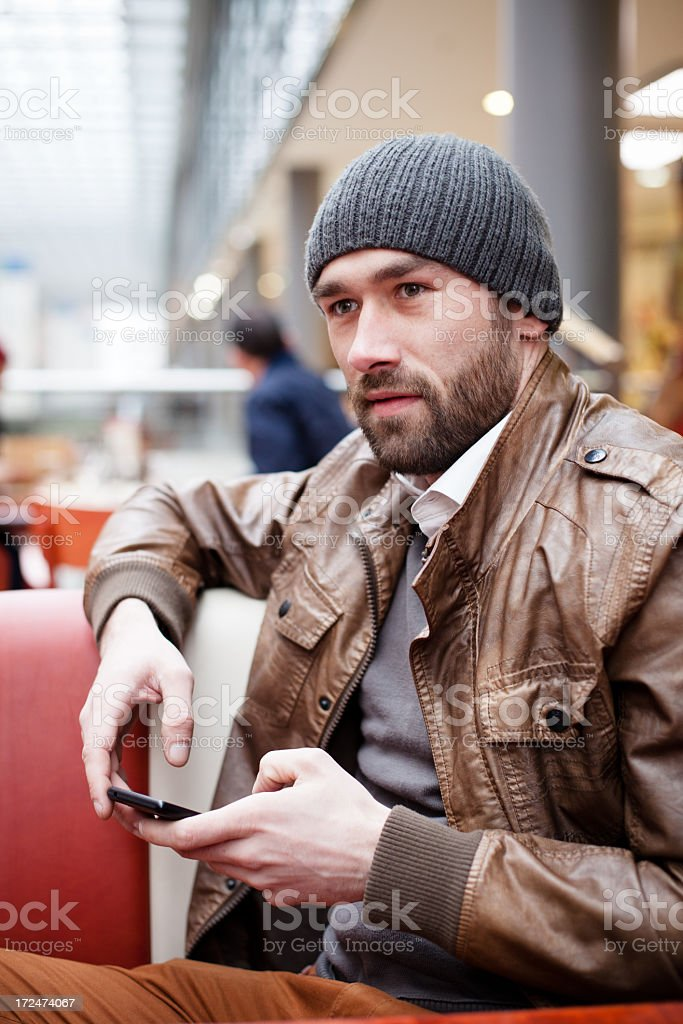 handsome man sits in cafe holds mobile phone in hands royalty-free stock photo