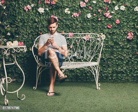 Handsome man sits on a vintage bench and typing text message, green wall of leaves and flowers on background.