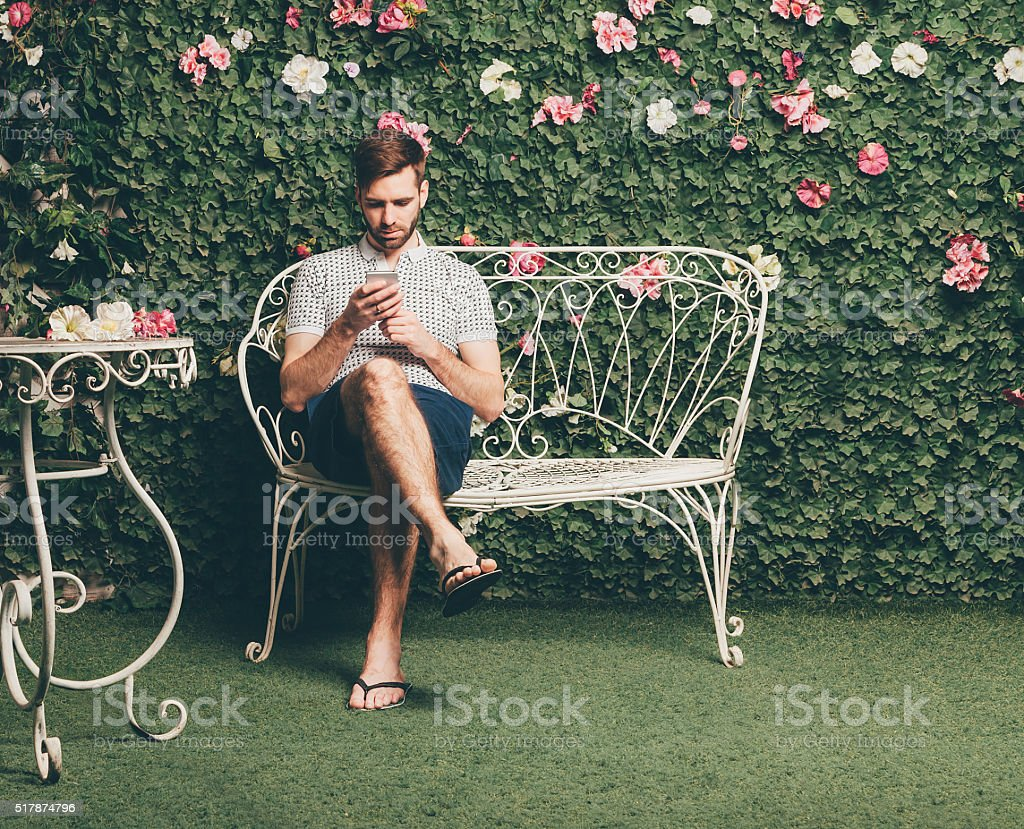 Handsome man sits on a bench and typing text message stock photo