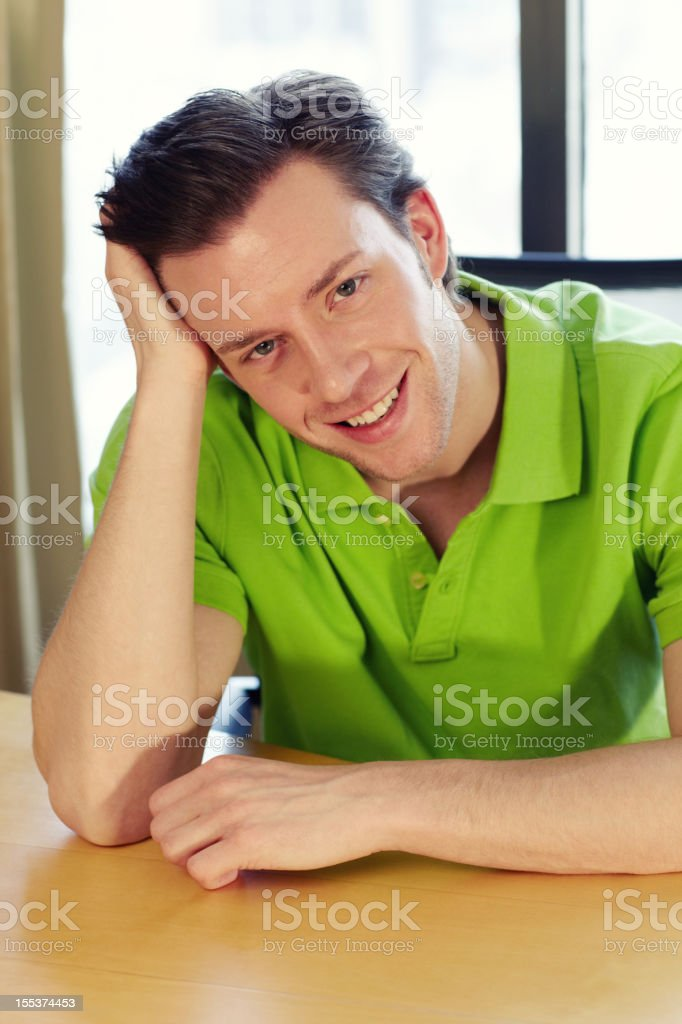 Handsome man sitting and smiling royalty-free stock photo