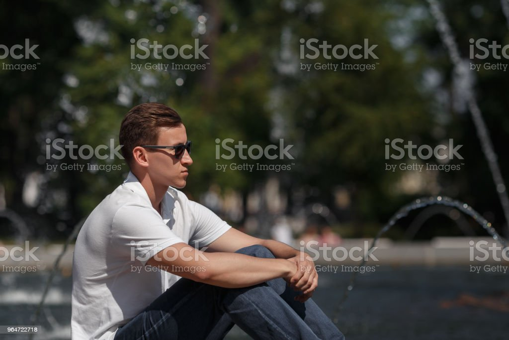 handsome man sitting in sunglasses near fountain royalty-free stock photo