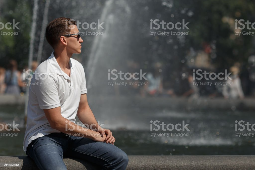 handsome man sitting in sunglasses on the fountain background, away from the camera royalty-free stock photo