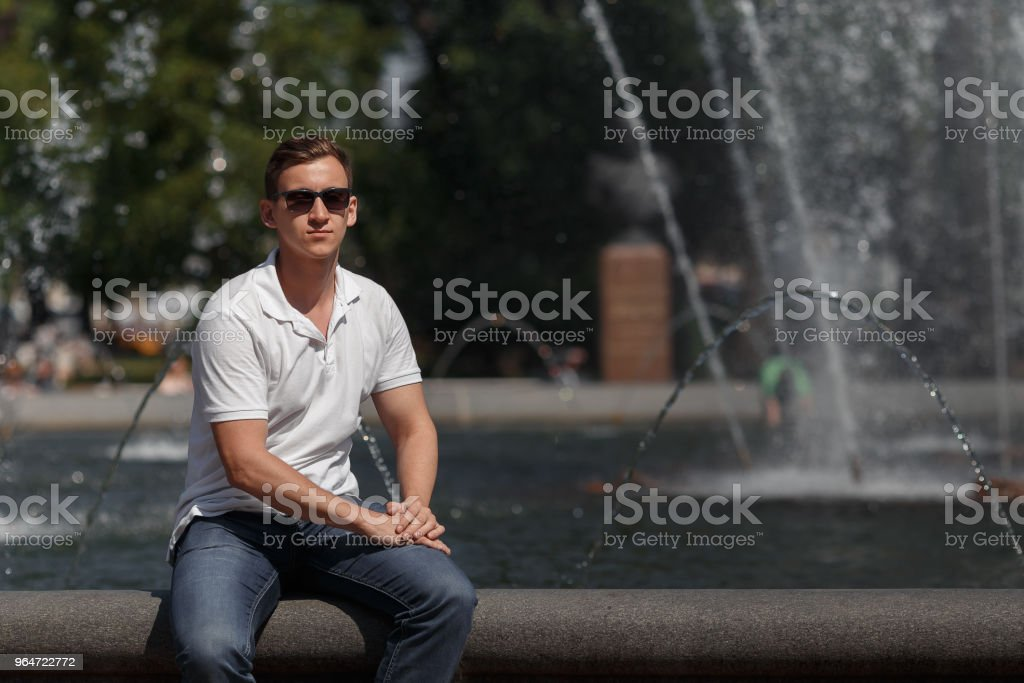 handsome man sitting in sunglasses on the fountain background, looking at the camera royalty-free stock photo