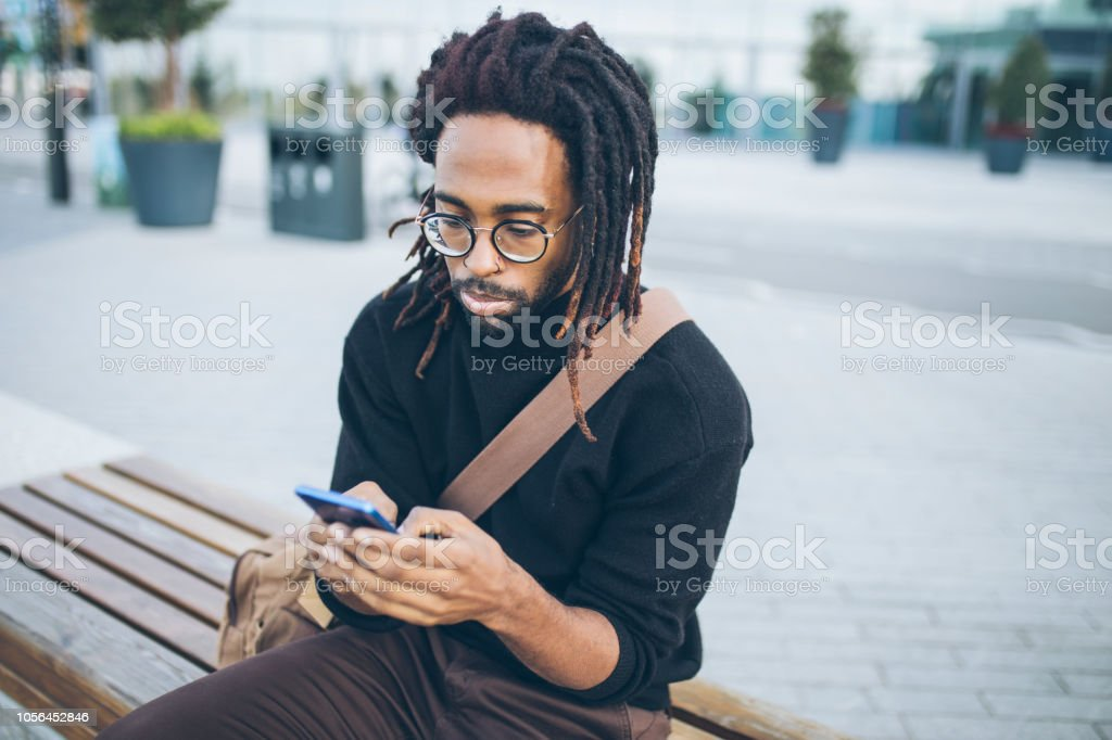 Handsome man sitting on a bench with a mobile phone stock photo