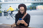 Modern african american businessman using tablet in front of office building outdoors