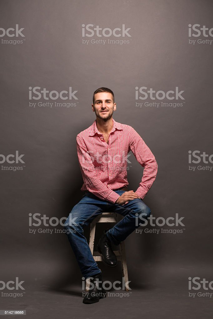 Handsome man sitting on a chair in studio stock photo