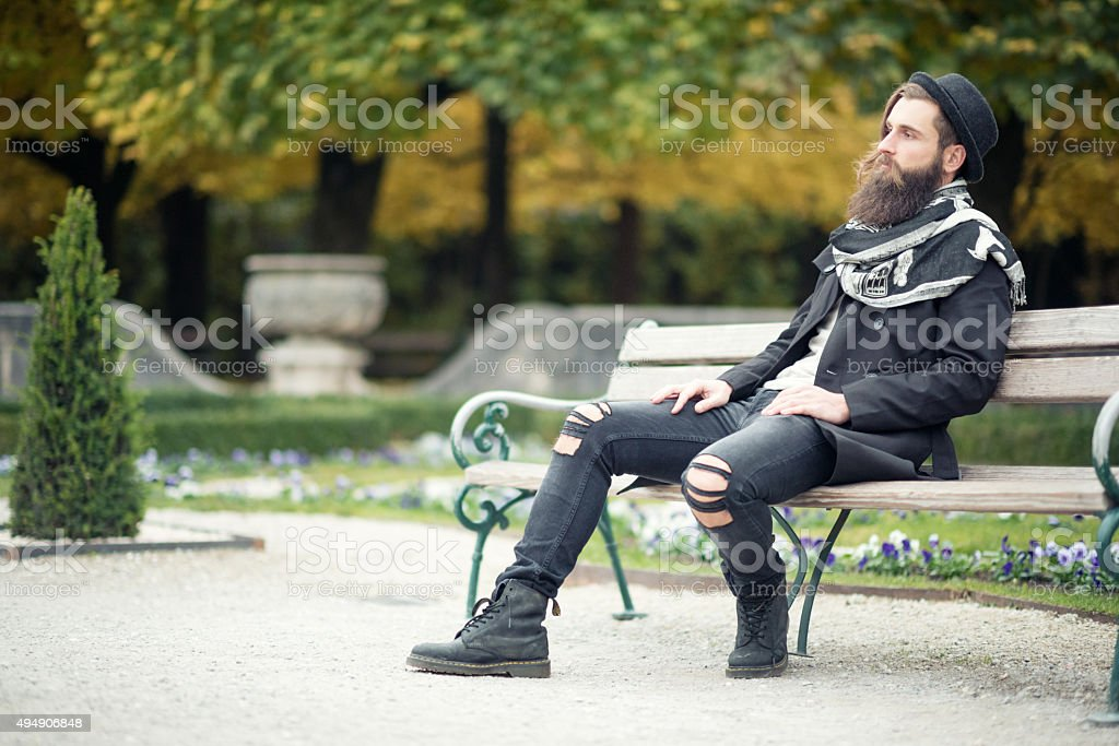 Handsome Man sitting on Park Bench, Male Fashion, Fall Colors stock photo