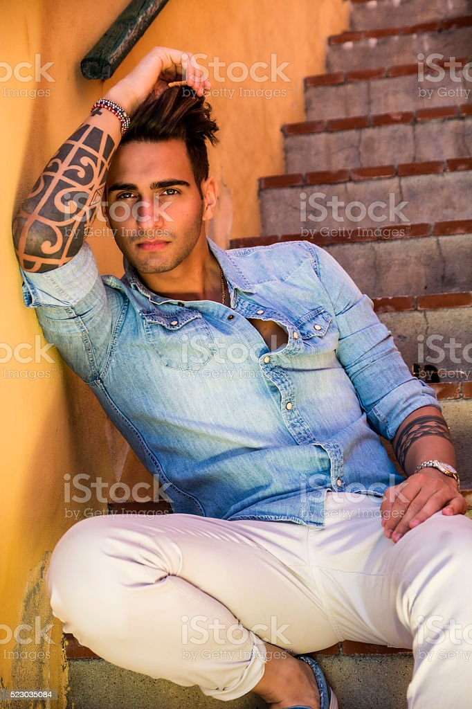 Handsome man sitting on stairs while looking at camera stock photo
