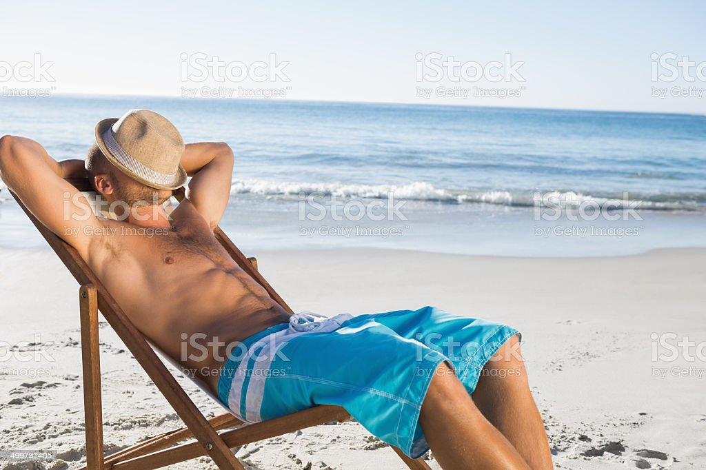 Handsome man sleeping on his deck chair stock photo