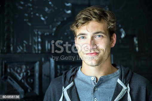Portrait of handsome man smiling against door. Young male is wearing casuals. He is at home.