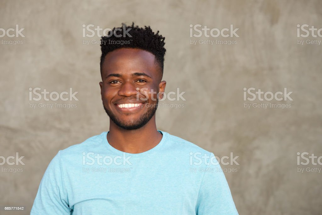 handsome man smiling and standing by wall stock photo