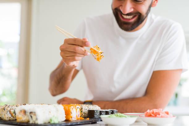 красивый человек улыбается счастливый наслаждаясь едой свежие красочные азиатские суши с использованием палочки для еды - food delivery стоковые фото и изображения