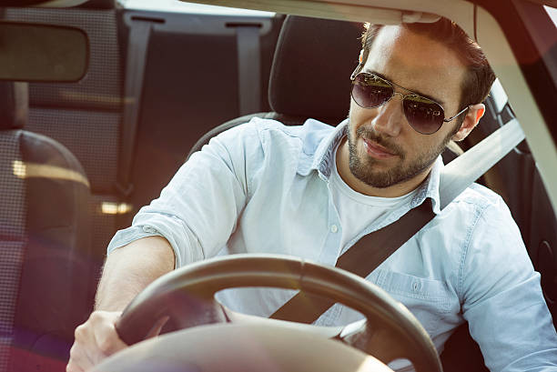gut aussehender mann lächelnd in auto - 1m coupe stock-fotos und bilder