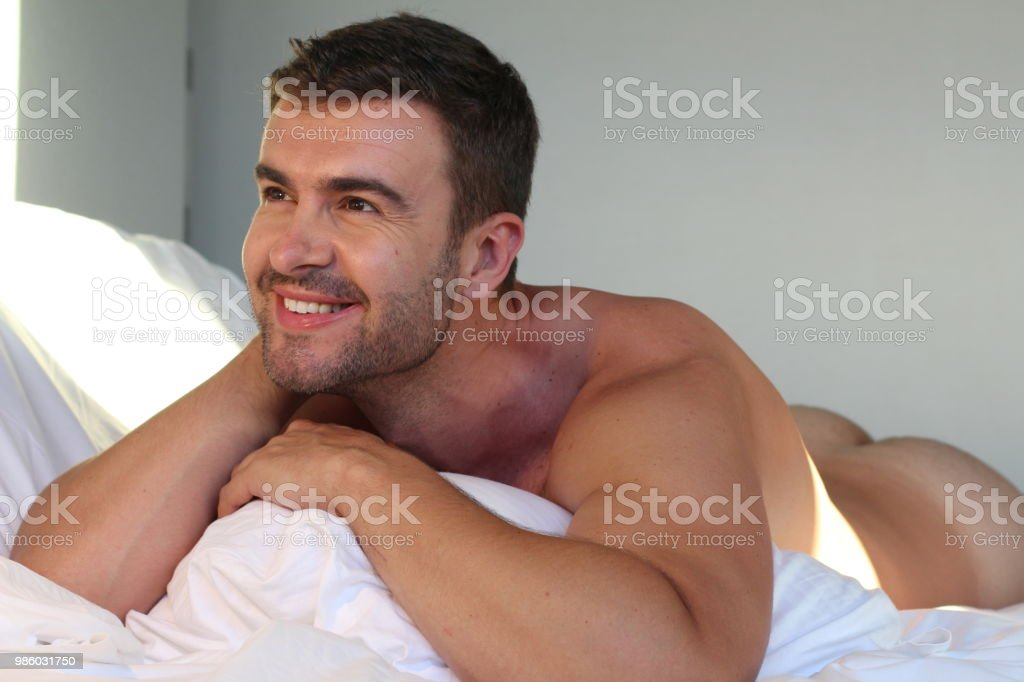 Handsome man smiling naked in bed stock photo