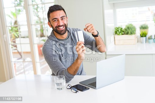 istock Handsome man smiling using credit card as payment metod when shopping online using laptop 1143702198