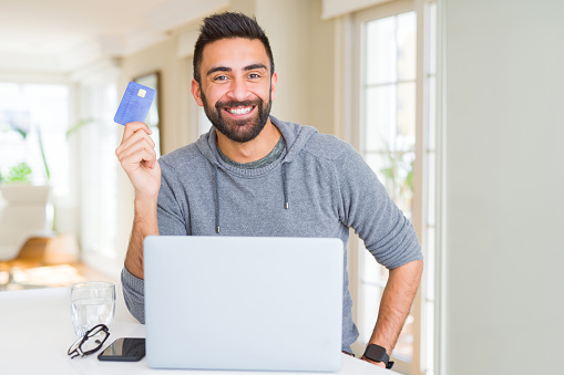 istock Handsome man smiling using credit card as payment metod when shopping online using laptop 1205747437
