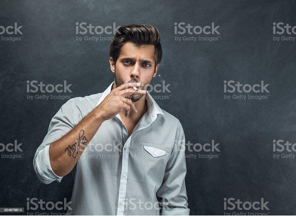 Handsome man smoking cigarette stock photo