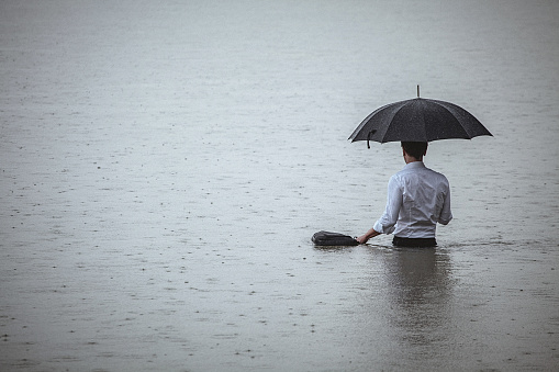 Rear view on a handsome man wearing white shirt and holding umbrella and a briefcase, standing in the water on a rainy day. The man waded knee-deep in water. Selective focus, three quarter length, copy space has been left.