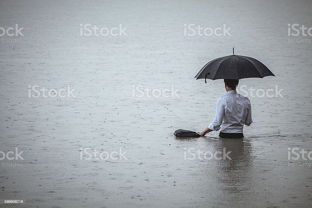 Handsome man standing in water and holding umbrella during rain stock photo