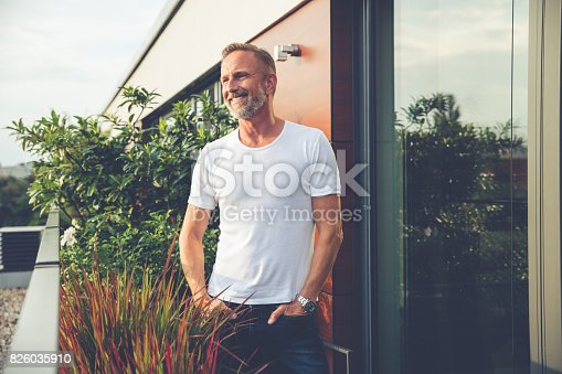 istock Handsome man standing on a balcony 826035910