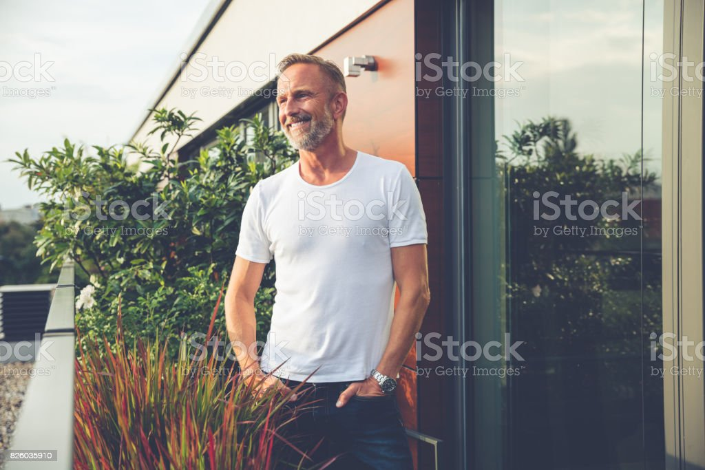 Handsome man standing on a balcony stock photo