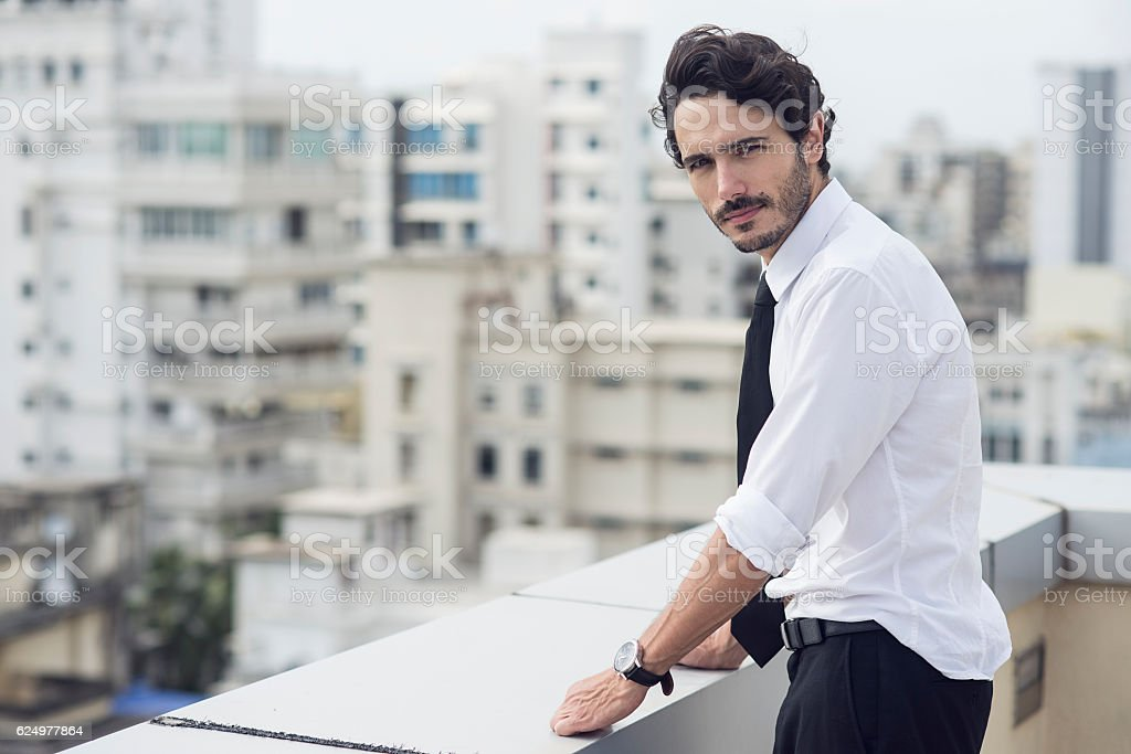 handsome man standing on the balcony stock photo