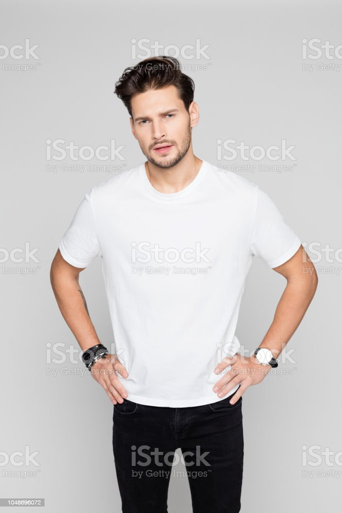 Handsome man standing with hands in hips Portrait of handsome man standing with hands in hips and looking at camera on grey background 25-29 Years Stock Photo