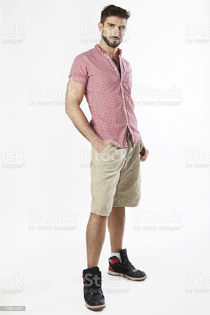 Handsome man standing with hands in pocket stock photo