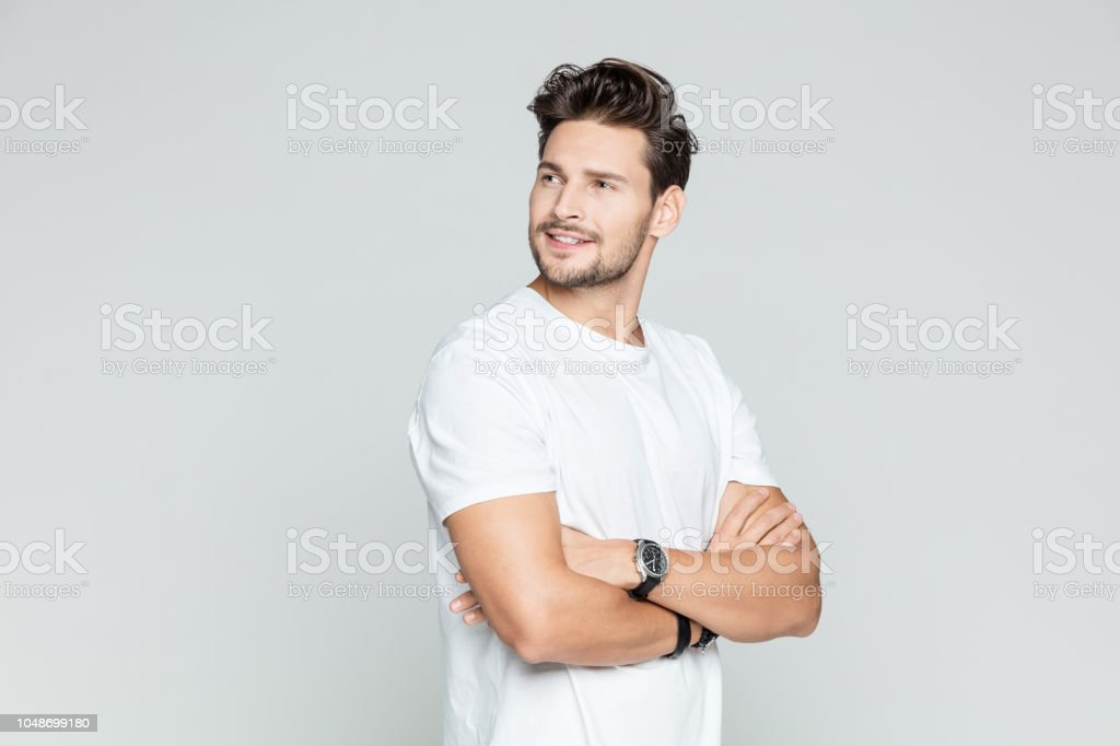 Handsome man standing with his arms crossed Portrait of handsome young man standing with his arms crossed looking away smiling on grey background. 25-29 Years Stock Photo