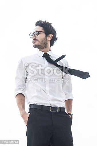 handsome man standing with his hands in pockets,wind blowing his tie