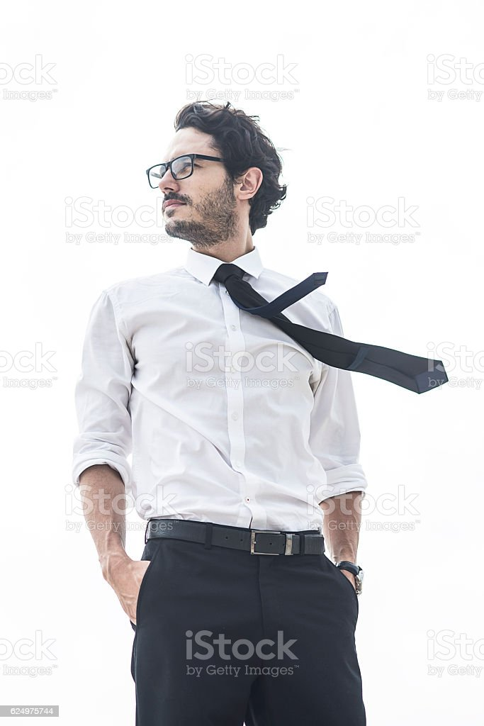 handsome man standing with his hands in pockets stock photo