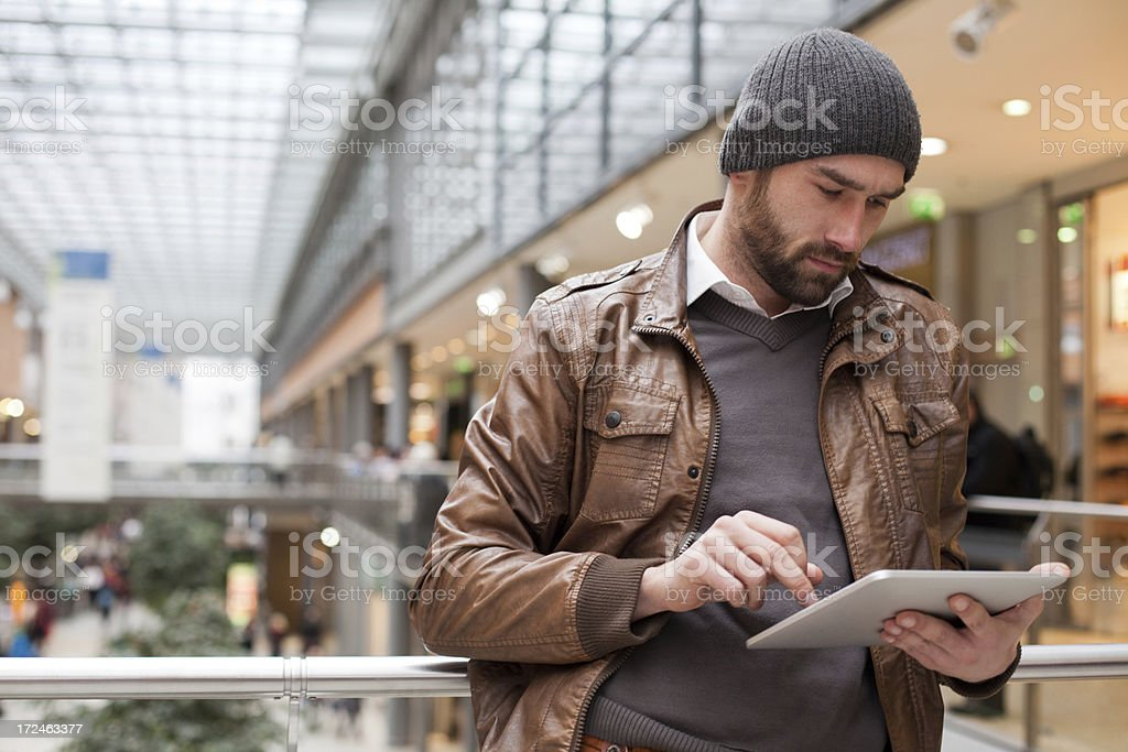 handsome man stands in a shopping mall holds digital tablet royalty-free stock photo