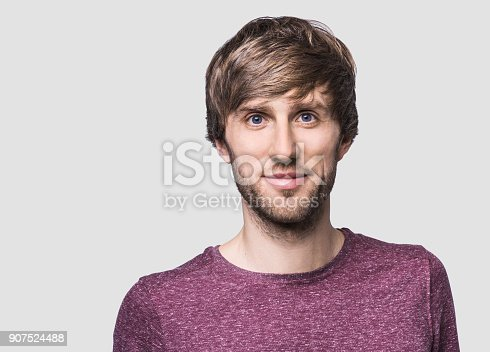 Cheerful young man smiling and looking to the camera. Isolated on gray background