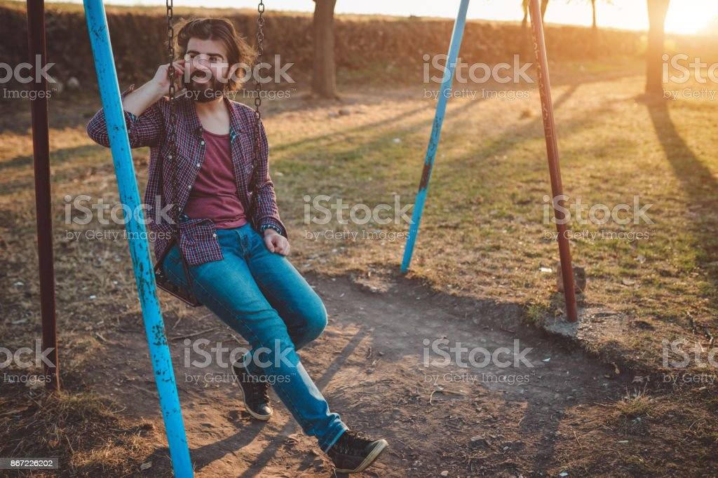Handsome man swinging on the swinging chair in the park and using mobile  phone - Stock image .