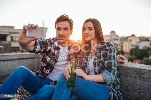 636330566istockphoto Handsome man taking a selfie with a woman holding a beer 976566322