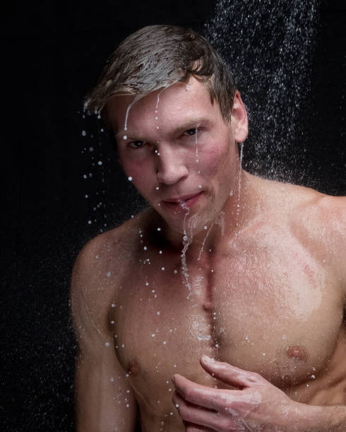 Handsome man taking a shower stock photo
