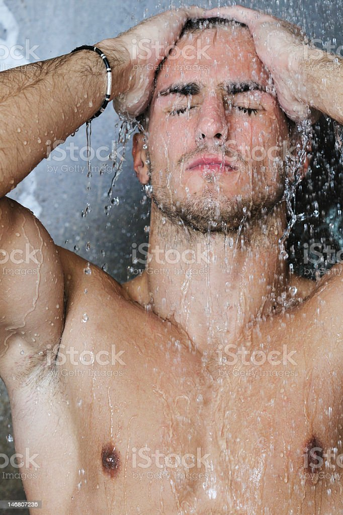 Handsome man taking a shower with the water running over him stock photo