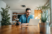 istock Handsome man taking notes and looking at laptop, at home office, portrait. 1250949597