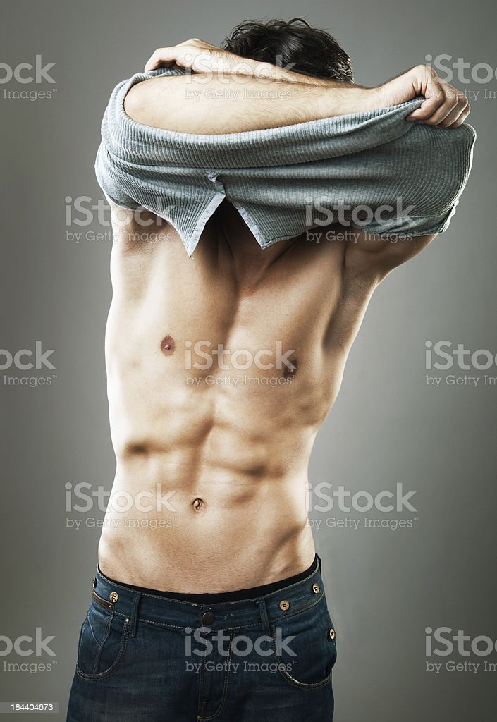 handsome man taking off his t-shirt royalty-free stock photo