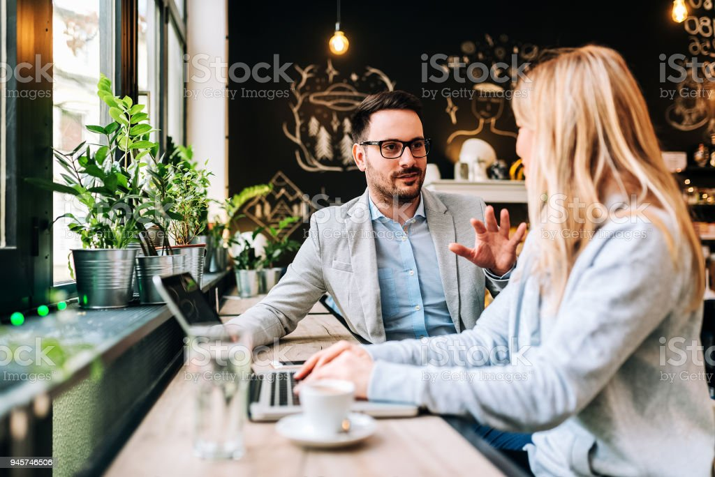 Handsome man talking to a young blonde woman at the cafe. stock photo