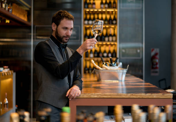 Handsome man tasting wine at a wine store looking very focused stock photo