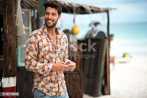 istock Handsome man text messaging. 918078946