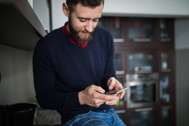Handsome man texting with his smartphone in kitchen picture id1184977651?b=1&k=6&m=1184977651&s=612x612&w=0&h=sfxumjucnjkeyorntwaxtmd2oe025jtrps1kiuwriyu=