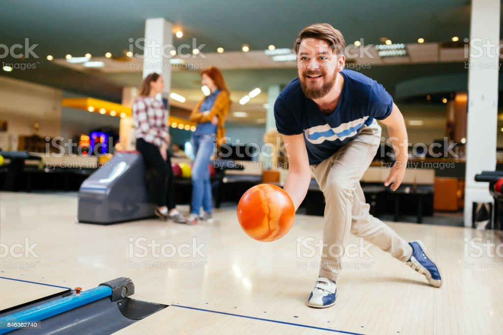 Handsome man throwing bowling ball stock photo