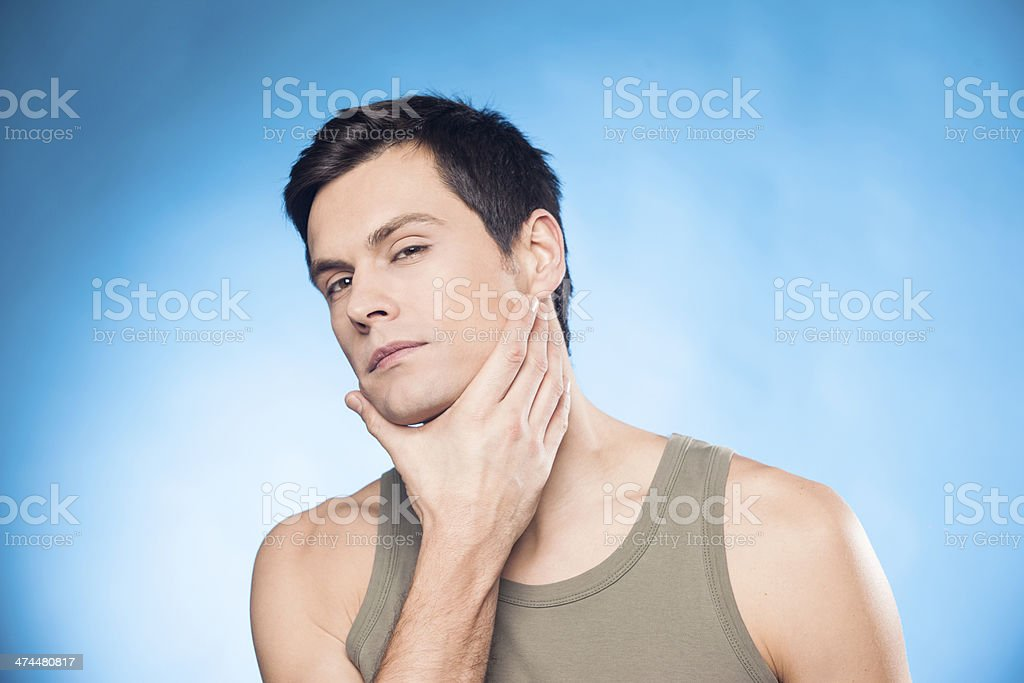 Handsome man touching his face stock photo