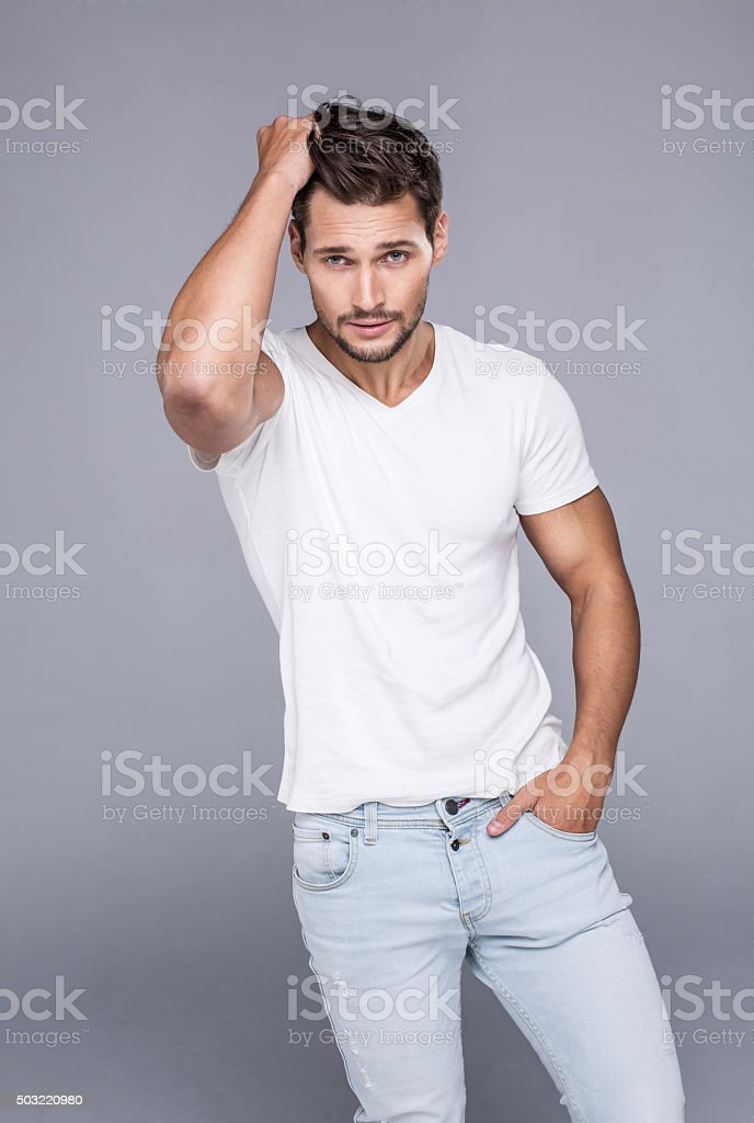 Handsome man touching his hair. Fashion model in white t-shirt stock photo