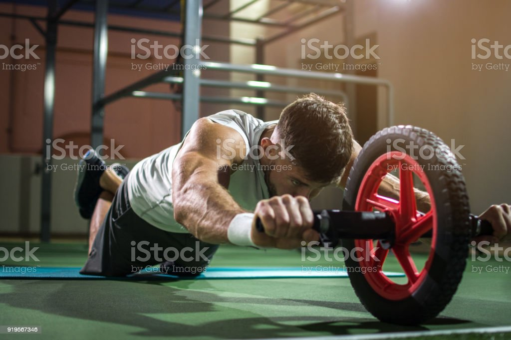 Handsome man training with wheel to strengthen his abdominal muscle. stock photo