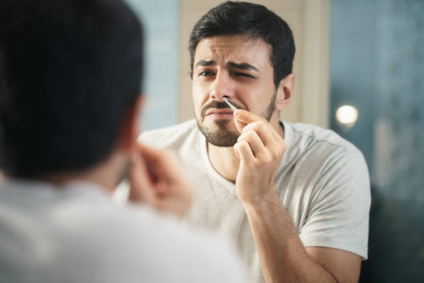 Handsome Man Trimming Nose Hair In Bathroom stock photo