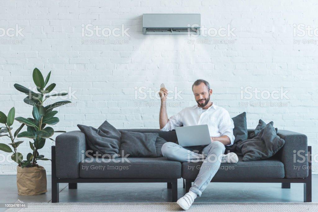 gut aussehender Mann, Klimaanlage mit Fernbedienung einschalten, während mit Laptop zu Hause auf sofa – Foto