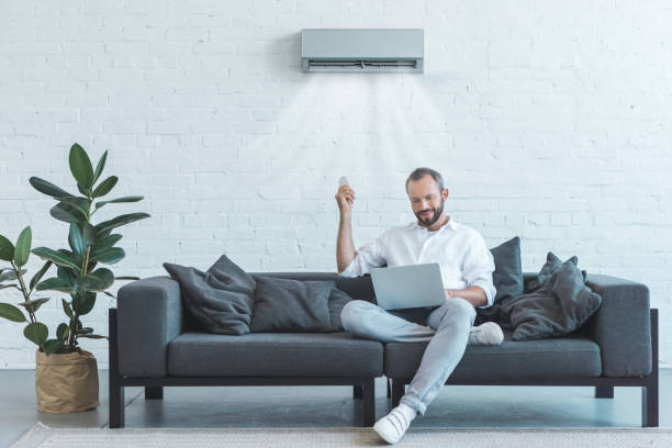handsome man turning on air conditioner with remote control while using laptop on sofa at home - guy sofa foto e immagini stock